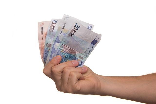 ruka drží vějíř eurových bankovek